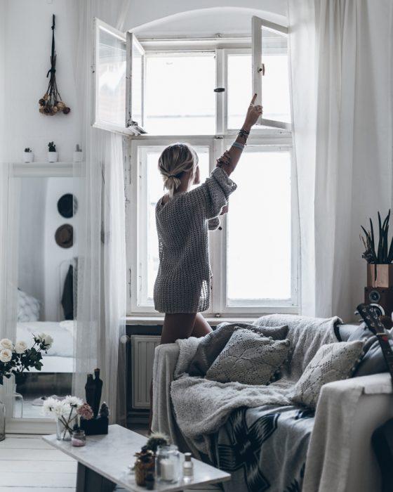 chica abriendo la ventanas de su departamento