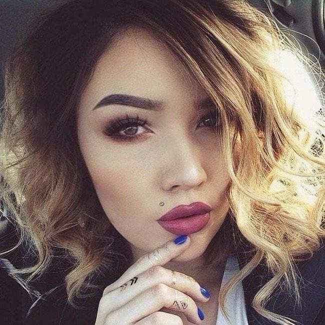 Chica usando un piercing sobre el labio en la parte superior izquierda