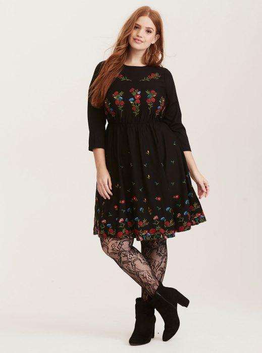 Chica usando un vestido en color negro con bordados florales