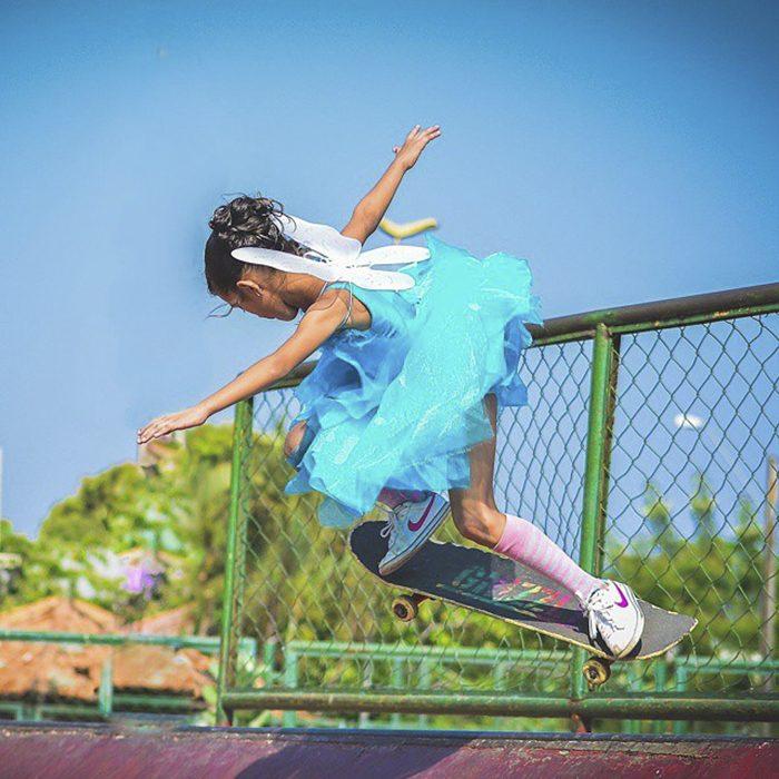 niña con vestido y alas en patineta
