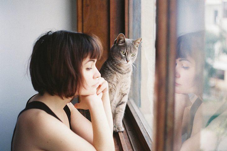 chic pensativa mirando por la ventana