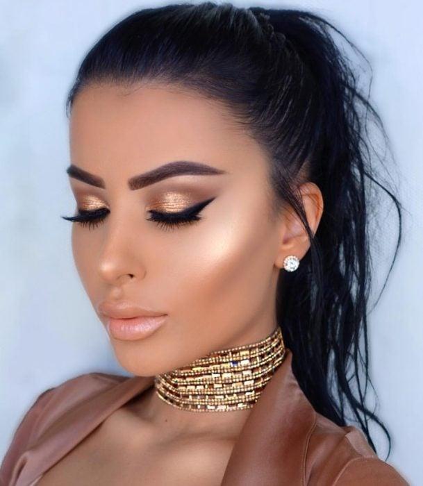Chica usando un maquillaje de color dorado con un delineado grueso