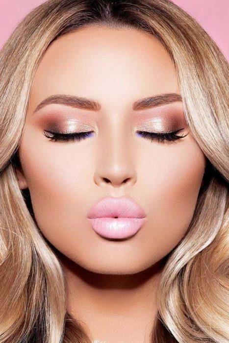 Chica usando una sombra de ojos dorada con un labial rosa nude