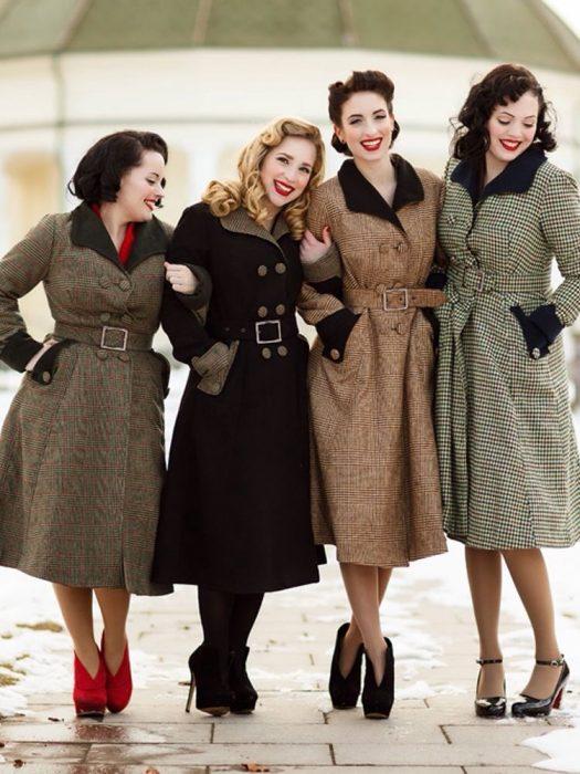 4 mujeres vestidas de pin up con abrigos