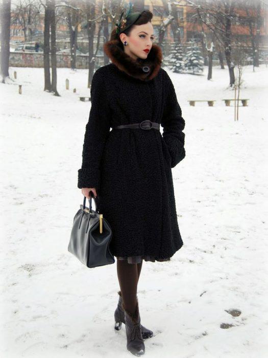 mujer con abrigo de peluche negro en la nieve