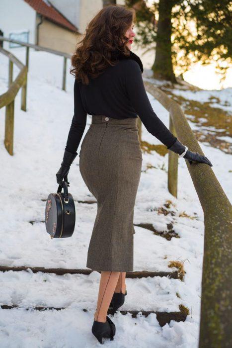 mujer con falda larga de espaldas y escaleras con nieve