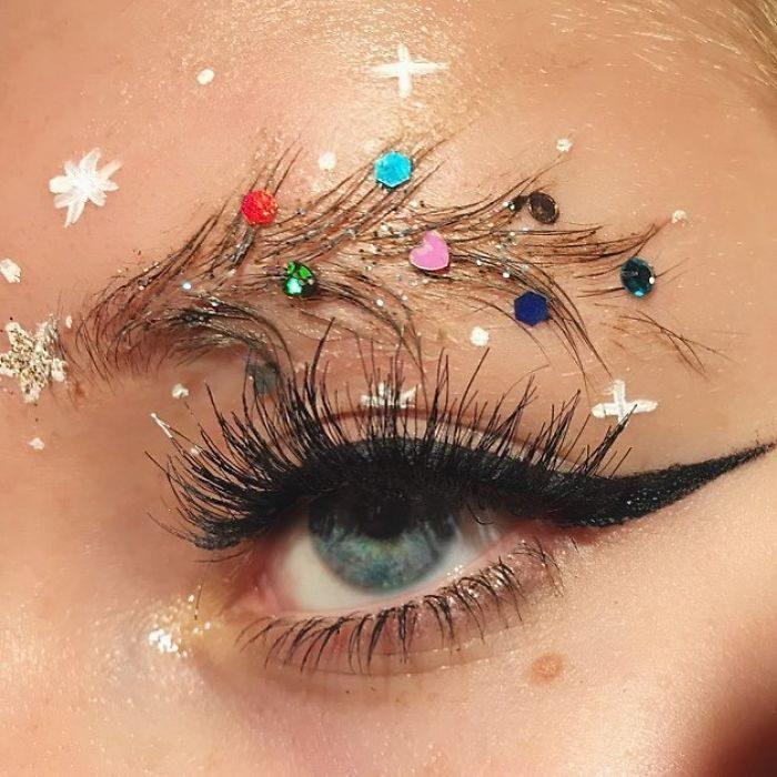 Chica con las cejas despeinadas y con decoraciones como si se tratara de un árbol de navidad