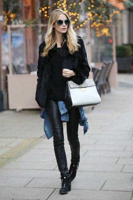 Chica usando unos pantalones de cuero y botines planos