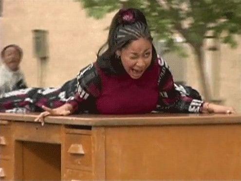 chica gritando arriba de una mesa