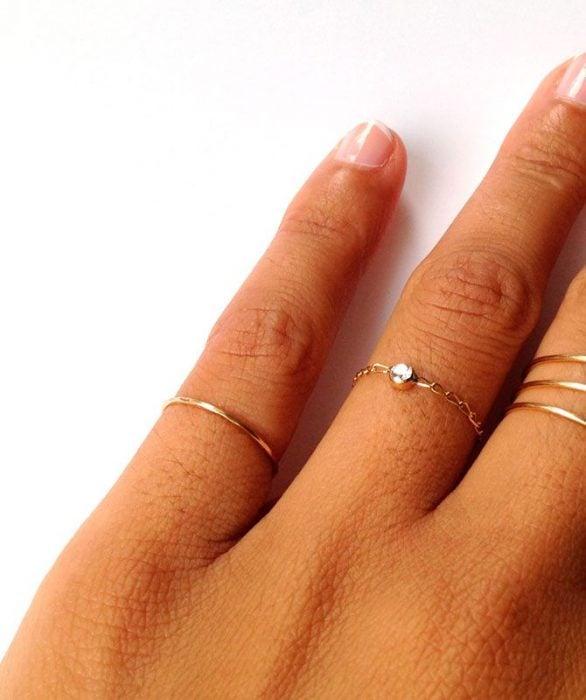 Chica usando anillos en todas sus manos
