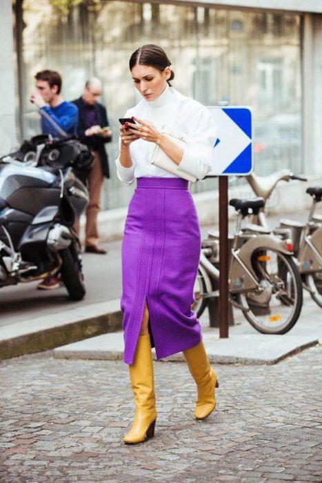 Mujer usando una falda morada y zapatos amarillos
