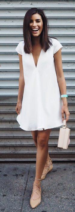 Chica usando un vestido blanco con flats de color cameo