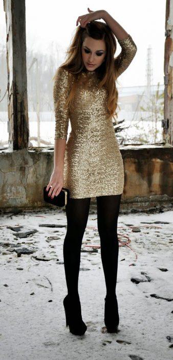 Chica usando un vestido dorado con medias negras