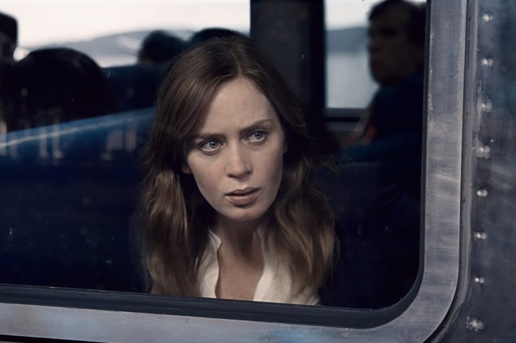 chica mirando por la ventana sospechosa