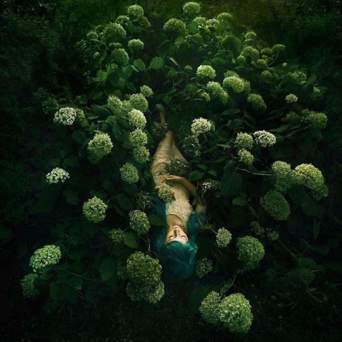 chica acostada sobre flores