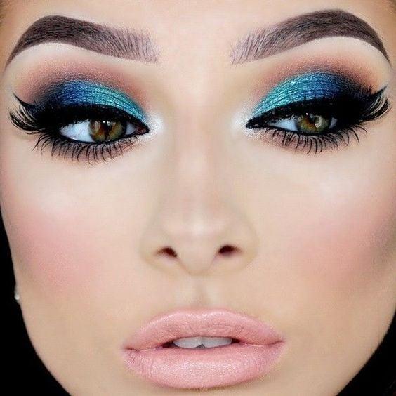 Chica usando una sombra de ojos verde y azul metálica