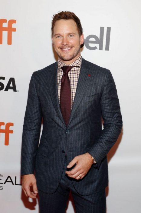 Chris Pratt sonriendo mientras usa un traje