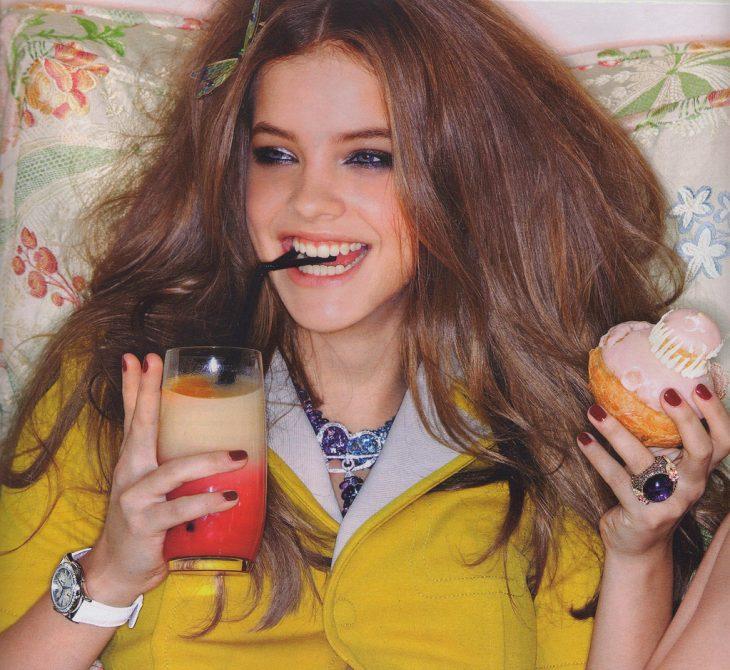 Chica comiendo una rosquilla y tomando jugo