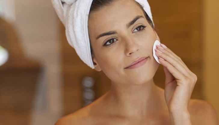 Chica aplicando crema en su rostro