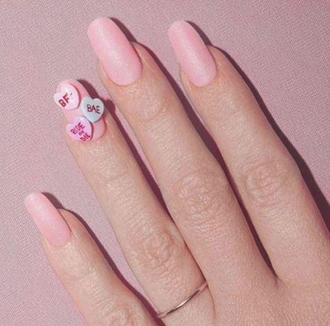 Uñas de Kim Kardashian en color rosa con aplicaciones de corazones
