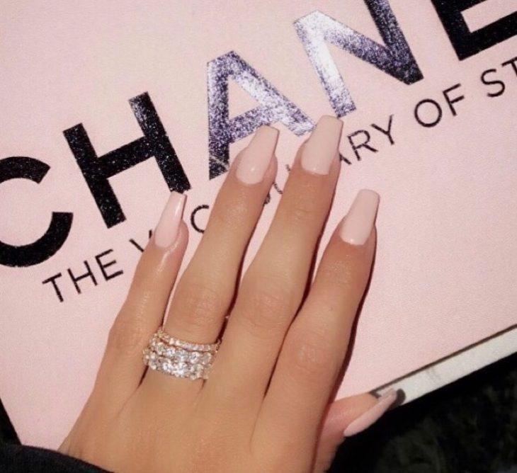 Uñas de color rosa sobre una caja de Chanel