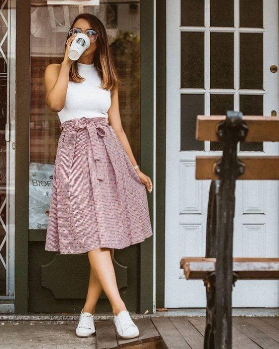 falda a la cintura con estampado blusa blanca y tenis