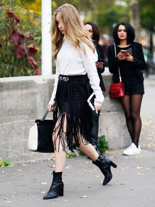 falda negra con flecos botines y blusa blanca
