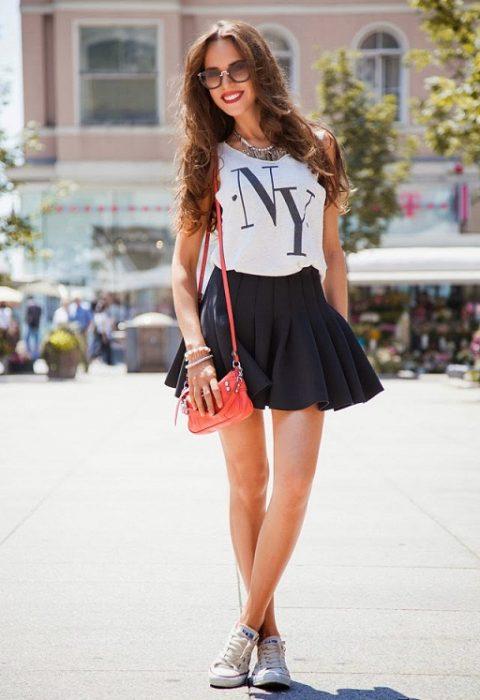 falda de tablas y blusa blanca estampado de NY y tenis chica castaña