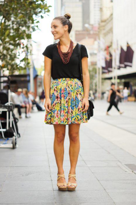 Minifalda estampada con tacones nude blusa negra