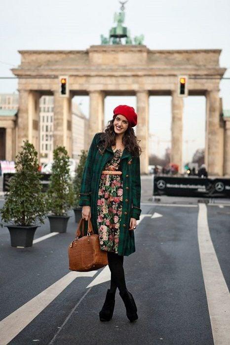 Chica con boina roja vestido de flores abrigo verde medias y botas negras