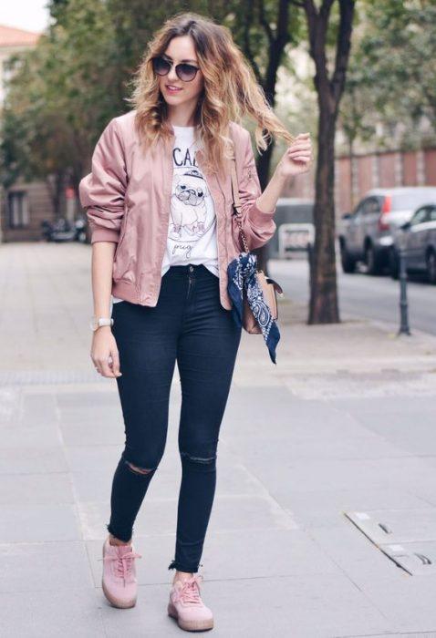 chica usando mezclilla, blusa estampada, tenis y chamarra rosa