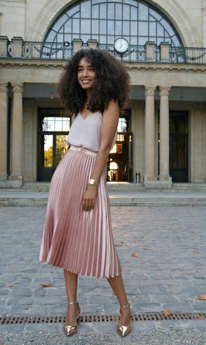 falda tableada rosa metalica, blusa de tejido ligero, chica cabello rizado