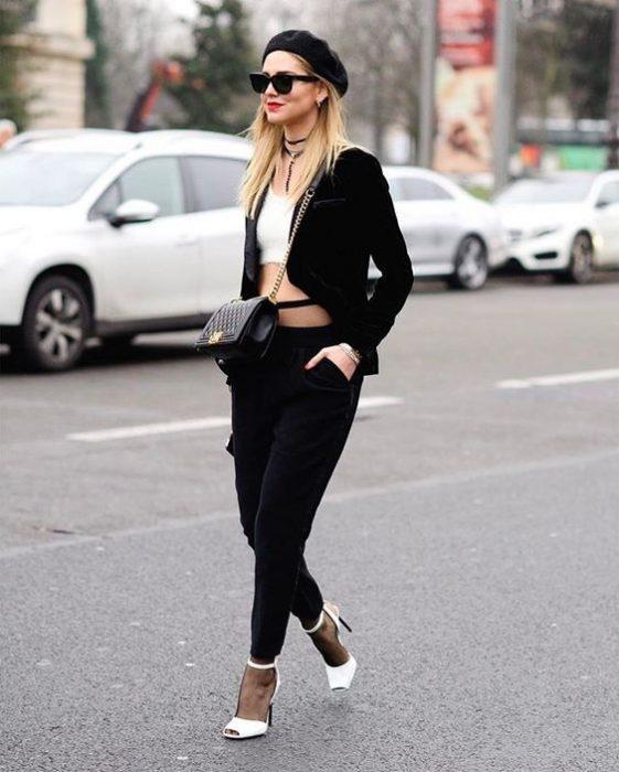 chica con pantalones y blazer negro croptop blanco zapatillas blancas y boina negra