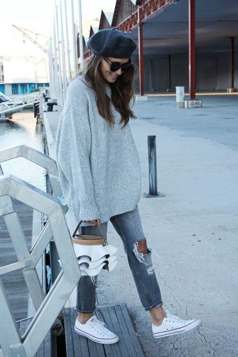 chica con pantalones desgarrados sudadera extra grande gris boina gris tenis converse blancos