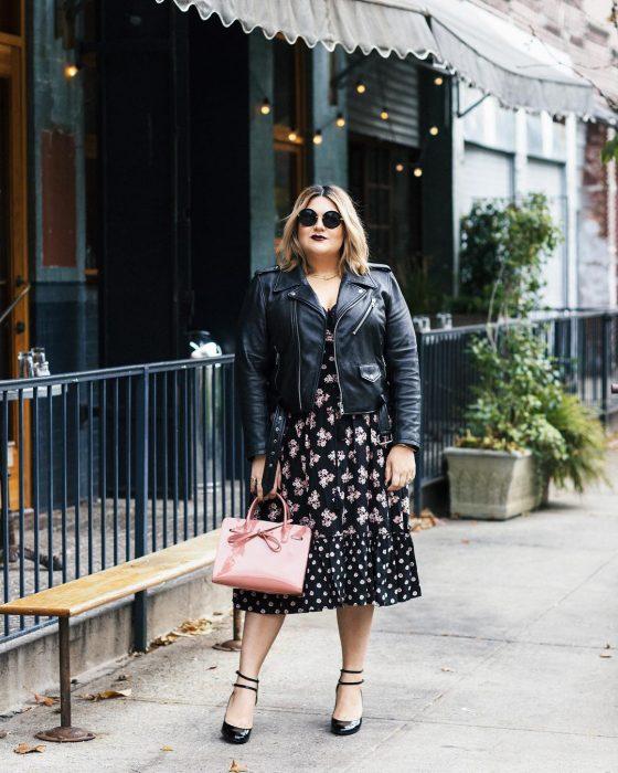 chica chubby con vestido negro con flores y bolso rosa pastel
