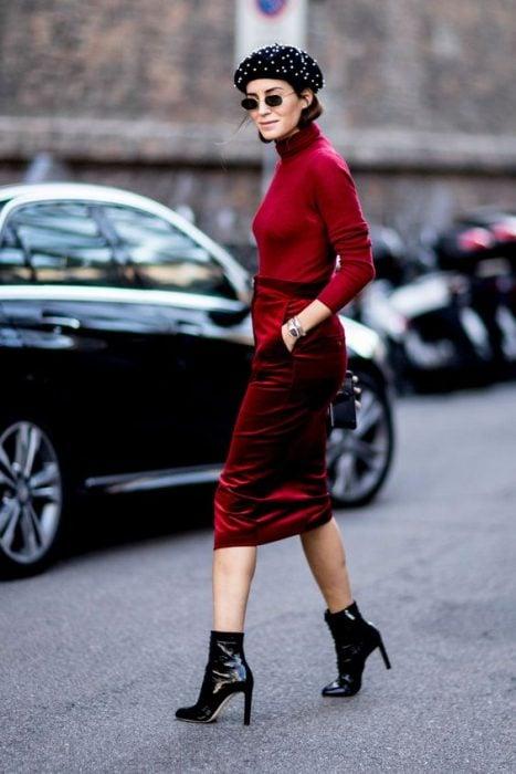 chica con falda lapiz de terciopelo rojo blusa cuello de tortuga roja boina negra botas de charol