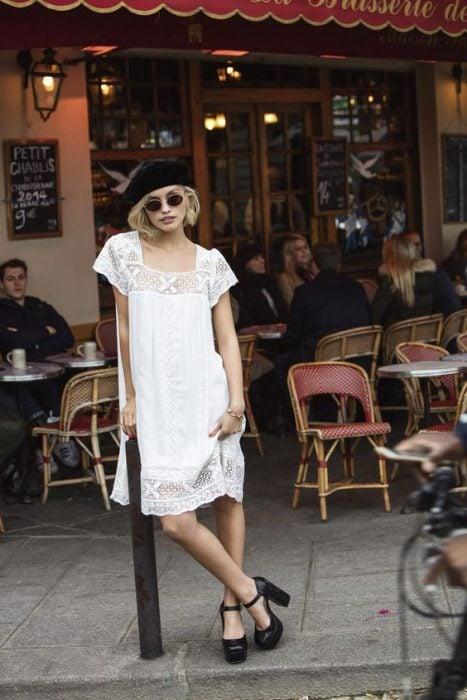 chica con vestido blanco veraniego tacones negros y boina negra