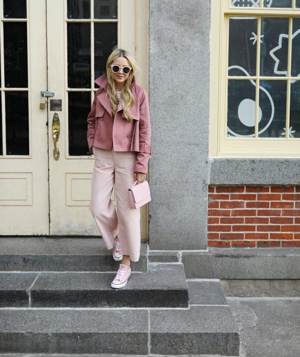 chica con pantalones rosa pastel y chaqueta rosa palo