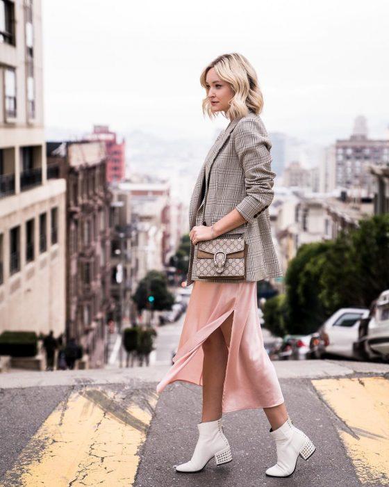 chica con falda rosa botas bancas y saco gris