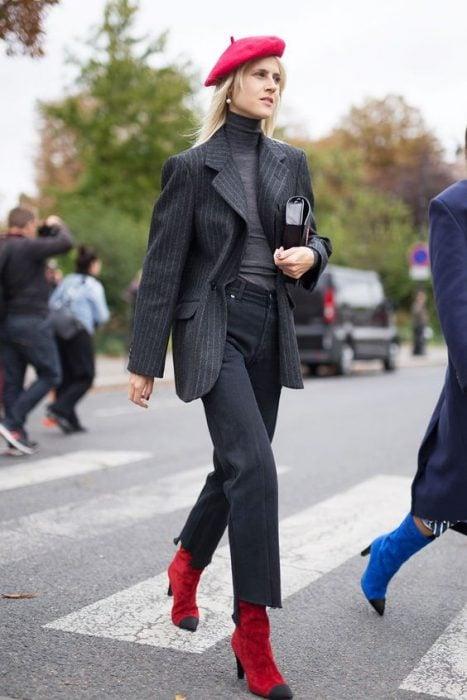 chica con pantalones de vestir blazer y blusa gris boina y botas rojas