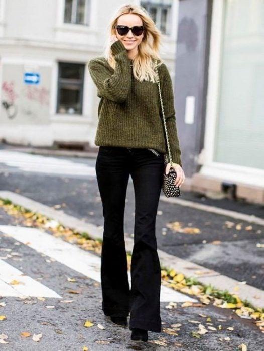 chica rubia con pantalones de campana negros y sueter verde
