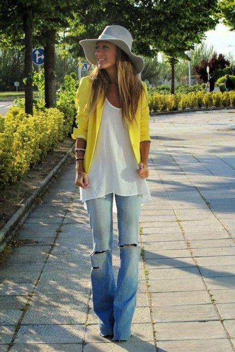 chica con blusa blanca sueter amarillo y pantalones de mezclilla rotos