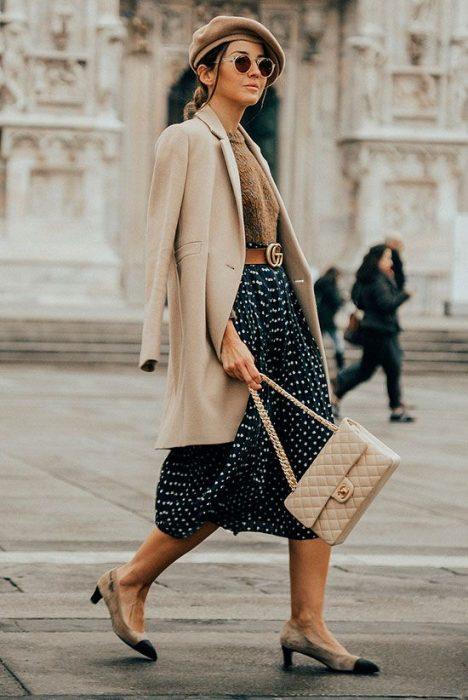 chica con falda de puntos, camisa, abrigo y boina camel