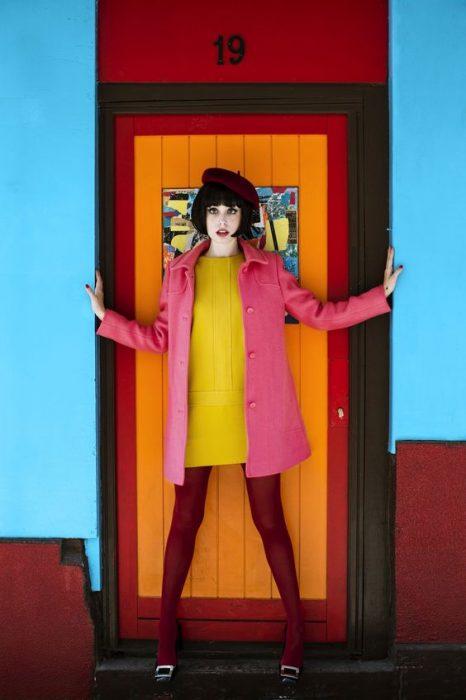 chica con boina y medias rojas vestido amarillo y abrigo rosa