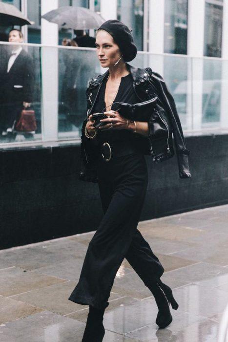 chica con jumpsuit negro chamarra de piel boina y botas negras