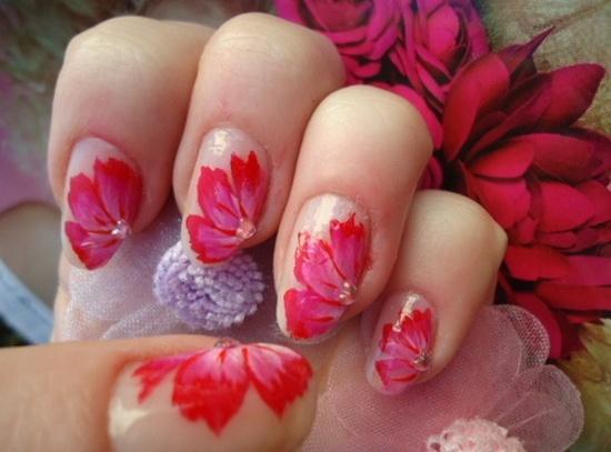 uñas con flores rojas sobre fondo trasparente
