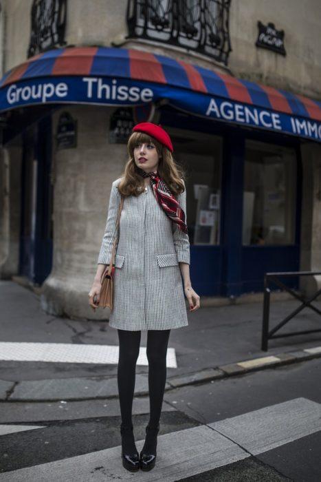 chica con medias, abrigo gris y boina roja