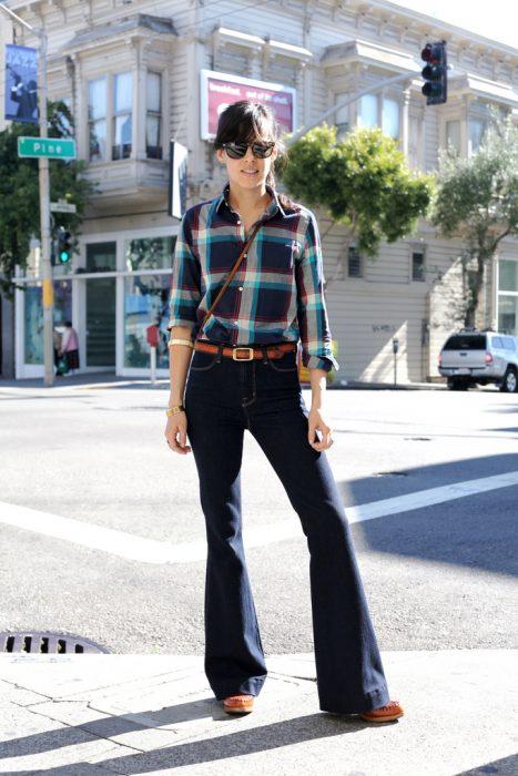 chica con pantalones de campana y cinto, camisa de cuadros