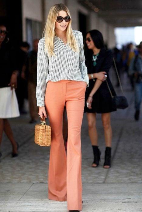 chica con pantalones de campana color durazno y blusa gris