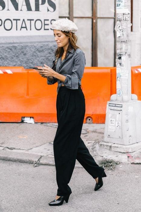 chica con pantalones sueltos blazer gris tacones negros y boina blanca